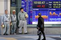 AP - A man checks the electronic stock board of a securities firm indicating Japan's Nikkei 225 stock average gained ...