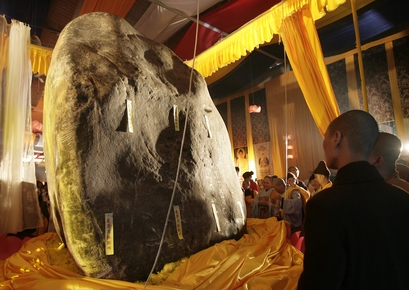 Buddhist monks look a the jade piece as it was unveiled on Monday, Jan. 18, 2010 in Hai Duong province, Vietnam. The jade imported from Myanmar measur