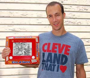 George Vlosich III holds an Etch a Sketch drawing he made of various Cleveland landmarks. He wears a graphic T-shirt designed by the art company he ow