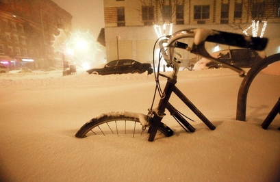 A bicycle is buried in snow in the early morning ...