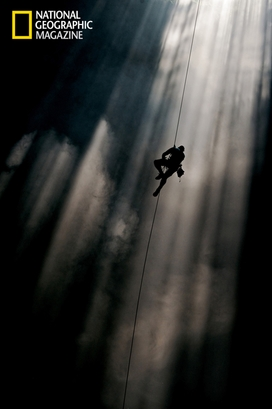 A climber ascends a shaft of light in Loong Con, ...