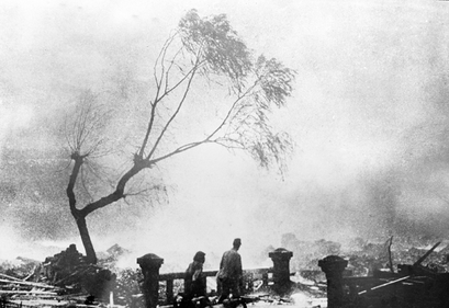 Survivors of the atomic bomb attack of Nagasaki walk through the destruction as fire rages in the background, Aug. 9, 1945. (AP Photo)