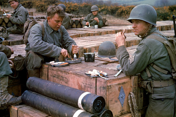 American combat engineers eat a meal atop boxes of ammunition...