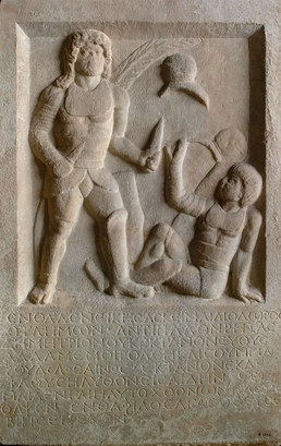 This 1,800-year-old tombstone depicts a gladiator holding two swords standing above his defeated opponent who is signaling submission. The inscription