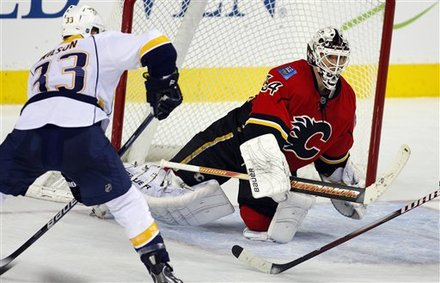 Nashville Predators' Colin Wilson, Left, Looks On As Calgary Flames Goalie Miikka Kiprusoff, From Finland, Swats Away