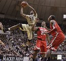 Purdue guard E'Twaun Moore (33), left, shoots over Ohio State forward David Lighty, center, and forward Deshaun Thomas in the first half of an NCAA college basketball game in West Lafayette, Ind., Sunday, Feb. 20, 2011. Purdue defeated Ohio State 76-63.