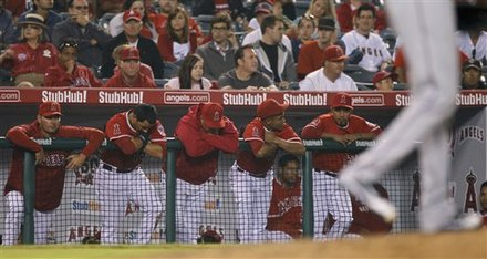 Members Of The Los Angeles Angels Hang On The Rail Of The Dugout