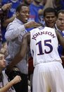 Kansas guard Tyshawn Taylor, left, welcomes guard Elijah Johnson (15) to the bench during the second half of an NCAA college basketball game against Oklahoma State in Lawrence, Kan., Monday, Feb. 21, 2011. Taylor is serving a suspension. Kansas defeated Oklahoma State 92-65.