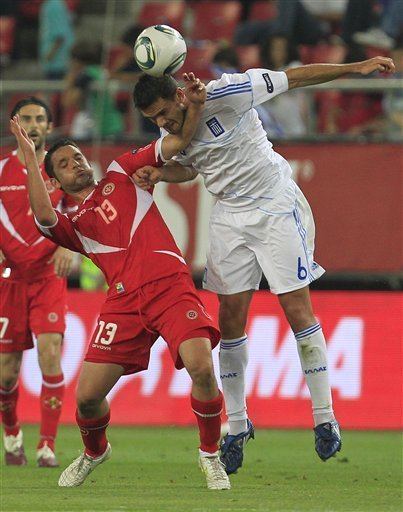 Alexandros Tziolis, Right, Challenge For The Ball With Andre Schembri Of Malta