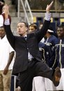 Pittsburgh head coach Jamie Dixon demonstrates the position his player, Cameron Wright, was in when a technical foul was called on Wright for hanging on the basket after dunking the ball in the first half of their NCAA college basketball game against Robert Morris on Sunday, Nov. 27, 2011, in Pittsburgh. Pittsburgh won 81-71.