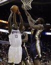 Charlotte Bobcats ' Nazr Mohammed (13) drives to the basket as Utah Jazz 's Al Jefferson , center, and Paul Millsap , right, defend during the first half of an NBA basketball game on Saturday, Nov. 13, 2010, in Charlotte, N.C.