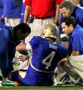 Tulsa quarterback G.J. Kinne (4) is attended to by team medical staff after a late hit in the first half during their NCAA college football game against Oklahoma State , Sunday, Sept. 18, 2011, in Tulsa, Okla. Kinne went to the locker room after suffering an apparent knee injury. The game was delayed by a severe thunderstorm.