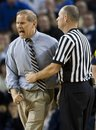 Michigan head coach John Beilein, left, is held back by an official while reacting to a referee's call in the second half of an NCAA college basketball game with Wisconsin , Wednesday, Feb. 23, 2011, at Crisler Arena in Ann Arbor, Mich. Wisconsin won 53-52.