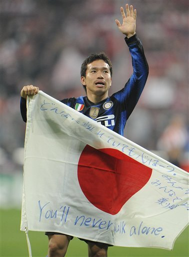 Inter's Yuto Nagatomo of Japan carries a flag of his country after winning the Champions League round of 16 second leg soccer match between FC Bayern Munich and Inter Milan in Munich, southern Germany, on Tuesday, March 15, 2010.