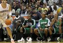Charlotte Bobcats forward Eduardo Najera (21) looks to score as Boston Celtics forward Kevin Garnett , second from left, guard Rajon Rondo , center,  guard Ray Allen , second from right, and forward Paul Pierce (34) sit on the  bench in the fourth quarter of an NBA basketball game in Charlotte, N.C., Saturday, Dec. 11, 2010. The Celtics won 93-62.