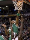 Boston Celtics ' Paul Pierce , top, scores over Toronto Raptors ' Reggie Evans during first half NBA basketball action in Toronto Sunday, Nov.  21, 2010.
