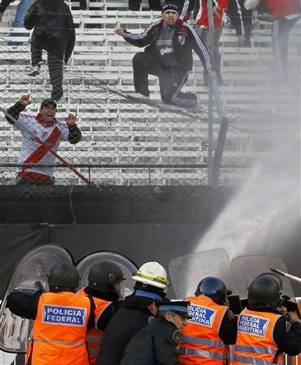 ALTERNATIVE CROP OF XNP130 - Police Spray Water At River Plate Soccer Fans To Keep Them From Jumping Over The Gate And