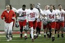 FILE - In this March 31, 2011 file photo, Ohio State defensive coach Jim Haycock, left, runs with a group of defensive players during the first day of NCAA college football practice in Columbus, Ohio. Even though most of the starters from a year ago have graduated, one of the biggest surprises at Ohio State this spring is the effectiveness of the Buckeyes defense.