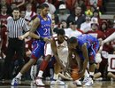 Kansas guard Josh Selby, left, and Oklahoma forward Andrew Fitzgerald, center, go for a loose ball as Kansas forward Markieff Morris, left, looks on in the second half of an NCAA college basketball game in Norman, Okla.,on Saturday, Feb. 26, 2011. Kansas won 82-70.