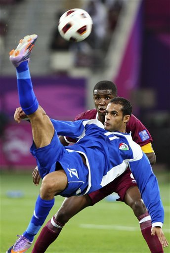 Kuwait - Bader Al Mutawa, front, fights for the ball