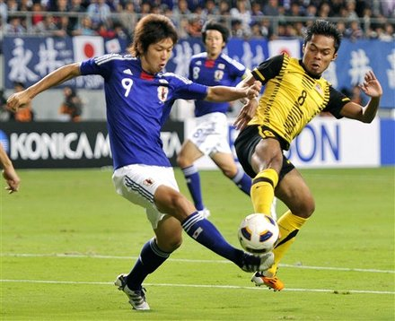 Japan's Yuya Osako, Left,  And Malaysia's Abdul Shukur Jusoh Vie For The Ball