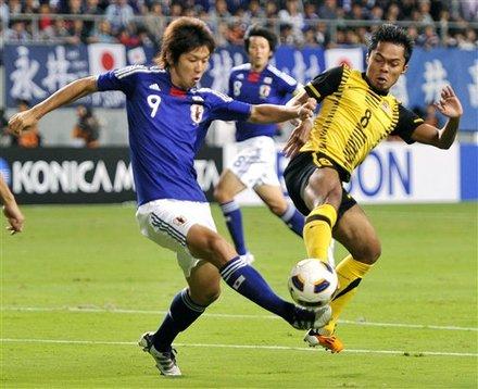 Japan's Yuya Osako, Left,  And Malaysia's Abdul Shukur Jusoh Vie For The Ball