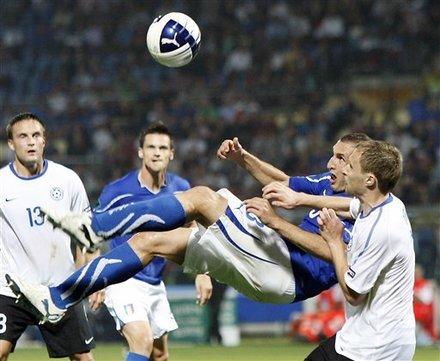 Italy Defender Giorgio Chiellini, Center, Performs A Scissor Kick As Estonia Midfielder Sander Puri Tries To Stop Him