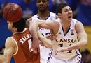 Kansas guard Tyrel Reed (14) and Texas guard Dogus Balbay (4) tangle for a rebound during the first half of an NCAA college basketball game in Lawrence, Kan., Saturday, Jan. 22, 2011.