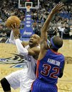 Orlando Magic 's Vince Carter , left, goes in for a shot as he is guarded by Detroit Pistons ' Richard Hamilton (32) during the first half of an NBA basketball game in Orlando, Fla., Tuesday, Nov. 30, 2010.