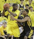 Michigan guard Tim Hardaway Jr. (10) is defended by Iowa forward Melsahn Basabe (1) during the first half of an NCAA college basketball game in Ann Arbor, Mich., Sunday, Jan. 30, 2011.