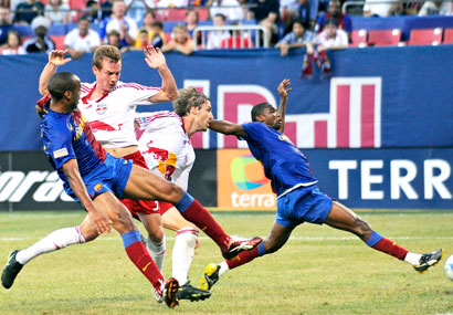 FC Barcelona forward Samuel Eto'o, right, takes a shot as as FC Barcelona forward Henry Thierry, left, New York Red Bulls defender Chris Leitch, second from left, and defender Jeff Parke look on during the first half.