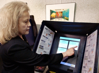 **FILE PHOTO** Deborah Clark, supervisor of elections in Pinellas County, demonstrates the voting procedure using a touchscreen voting machine during a news conference, July 27, 2004, in Tallahassee, Fla.  (AP Photo/Phil Coale)