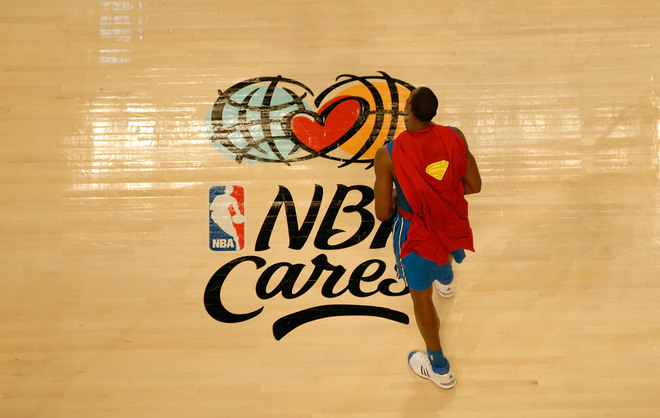 NEW ORLEANS - FEBRUARY 16: Dwight Howard of the Orlando Magic walks across the NBA Cares logo wearing a Superman cape during the Sprite Slam Dunk Contest part of 2008 NBA All-Star Weekend at the New Orleans Arena on February 16, 2008 in New Orleans, Louisiana. NOTE TO USER: User expressly acknowledges and agrees that, by downloading and or using this photograph, User is consenting to the terms and conditions of the Getty Images License Agreement. Mandatory Copyright Notice: Copyright 2008 NBAE (Photo by Juan Ocampo/NBAE/Getty Images)