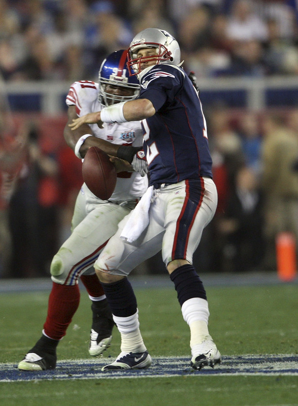 GLENDALE, AZ - FEBRUARY 03: Tom Brady #12 of of the New England Patriots fumbles the ball in the second quarter as he is hit by Justin Tuck #91 of the New York Giants during Super Bowl XLII on February 3, 2008 at the University of Phoenix Stadium in Glendale, Arizona. (Photo by Andy Lyons/Getty Images)