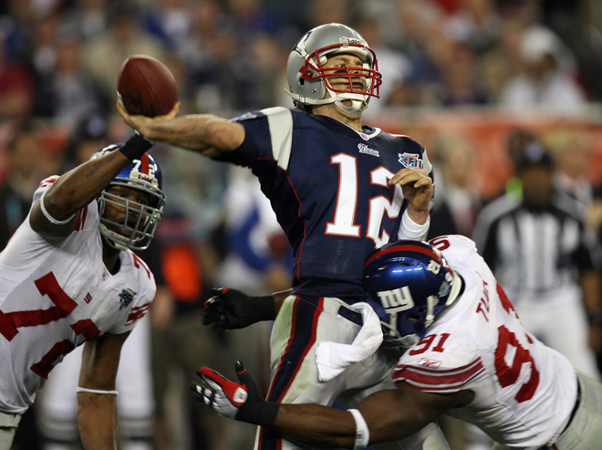 New England Patriots quarterback Tom Brady (C) passes the ball despite Osi Umenyiora (L) and Justin Tuck of the New York Giants during Super Bowl XLII at the University of Phoenix Stadium 03 February 2008 in Glendale, Arizona. AFP PHOTO / GABRIEL BOUYS (Photo credit should read GABRIEL BOUYS/AFP/Getty Images)